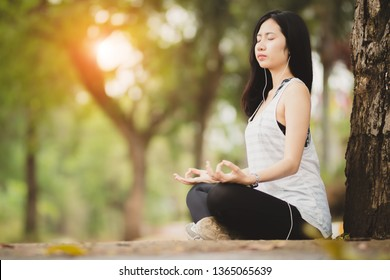 Asia woman ,girl listening to music and do meditation in the park,garden with happy.