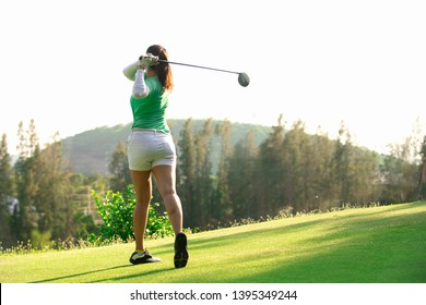 Asia woman golfer playing golf at golf course ,Golfer hitting golf ball , Healthy Holiday Concept