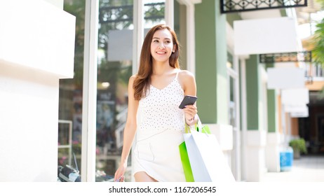 Asia woman holding many shopping bags and smart phone at shopping mall
