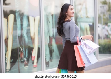Asia Woman holding many shopping bags at shopping mall