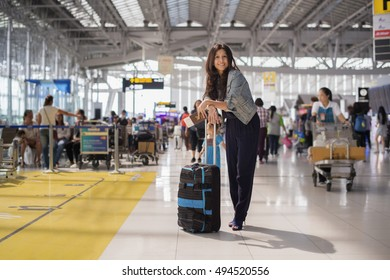 Asia woman at international airport, holding passport , ticket, luggage and waiting for her flight and background blur passenger.