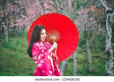 Asia woman with kimono and red Japanese umbrella against sakura flower background