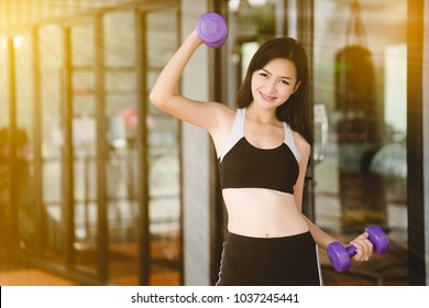 Asia Woman lifting dumbbell. Exercise to tighten the muscles. Keeps your body healthy and youthful. playing must have the right knowledge. If you play the right way, it will have a beautiful shape.