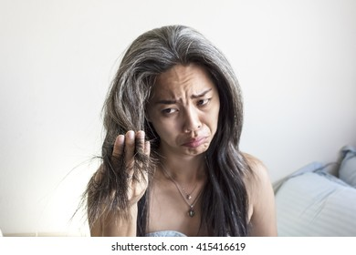 Asia woman is not happy with white fragile and damaged hair on bed, in selective focus on white background for text