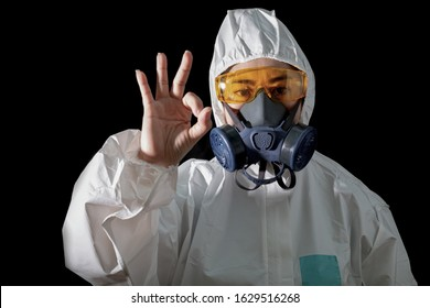Asia woman o.k hand sign in a chemical protective clothing and  Woman in chemical protective clothing and half mask replaceable particulate filter respirator  with glasses at black background