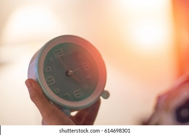 Asia woman on bed head on pillow hand holding white teal round alarm clock at 5.00 a.m. in morning as bio clock usually wake up on time with light effect in bedroom. Biological Clock Day in April 28th