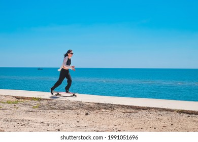 Asia woman playing longboard near the beach on vacation