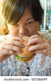 Asia woman plump body eating a hamburger is a unhealthy food at fastfood , process in soft orange sun light style