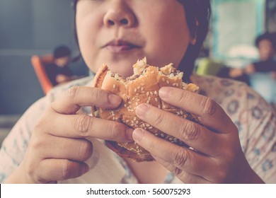 Asia woman plump body eating a hamburger is a unhealthy food at fastfood , process in vintage style