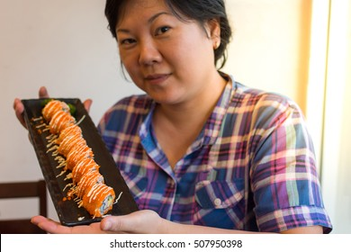 Asia woman plump body holding california roll on dish in japanese food buffet restaurant. , process in soft orange sun light style