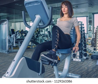 Asia woman put sport wear working out on exercise bike at the gym. Female exercising on bicycle in health club