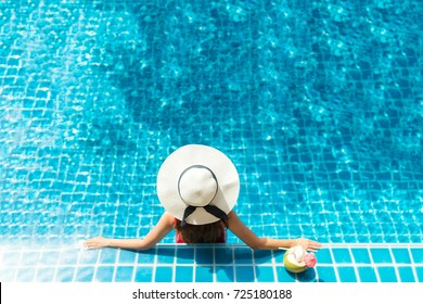 Asia woman relaxing on donut lilo in the pool water in hot sunny day. Summer holiday idyllic