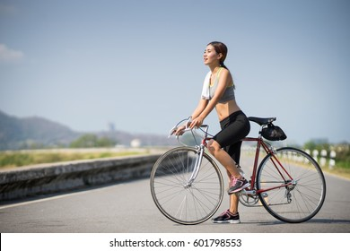 Asia woman ride a bicycle race style sport, copy space on Left side.