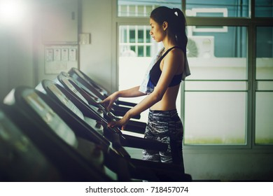 asia woman running in machine treadmill at fitness gym