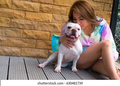 Asia woman sitting in the floor of Balcony with french bulldog living in house with dog. Heat Stroke and Hyperthermia in Dogs,Take care and love dog, kiss the dog