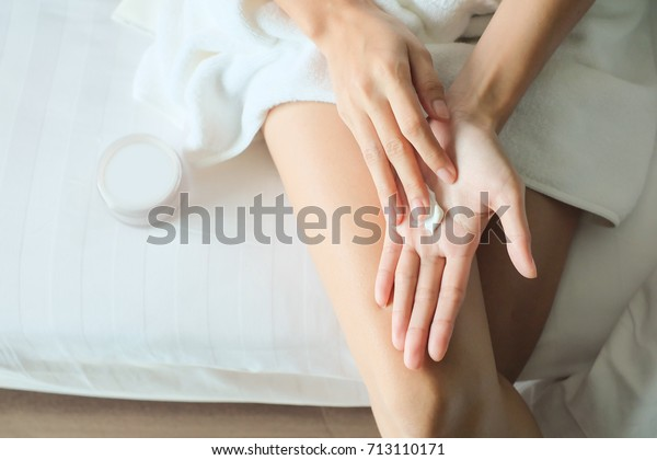 Asia woman sitting on bed and applying cream on Hand.