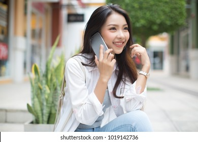 Asia woman sitting and talking with smart phone in the street in a sunny summer day