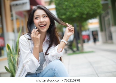Asia woman sitting and using a smart phone in the street in a sunny summer day