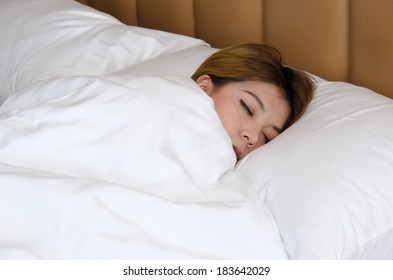 Of Asia woman sleeping on white bed.
