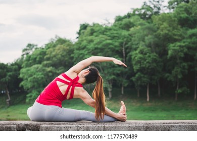 Asia woman with sport bra doing yoga fitness exercise for relax and healthy at lake in morning, Nature background, Concept outdoor sport and health