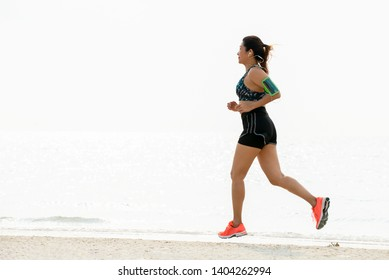 Asia woman in sports bra  listening to music on smartphone armband jogging on the beach. Fitness female  runner running in morning at sea , summer healthy active lifestyle concept