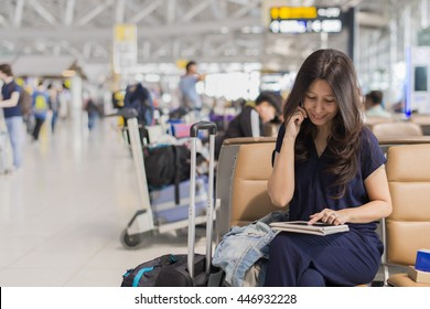 asia woman talking mobile phone and using her tablet computer while waiting for her flight on blur airport terminal background.