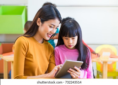 Asia woman teacher teach girl student with tablet computer in classroom at kindergarten preschool,Online education concept,e-learning