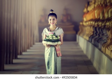 Asia woman in Thai dress traditional hold kratong.
