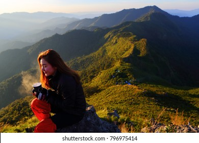 Asia woman traveler drinks coffee with a view of the mountain landscape