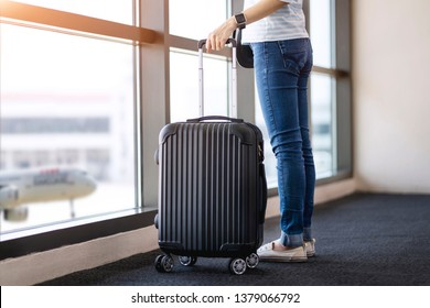 Asia woman traveler with suitcase waitting flight at airport. Travel weekend vacation.