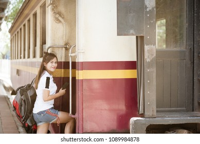 Asia woman traveller feeling happiness using smartphone while waiting for a train at train station.