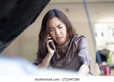 asia woman upset and angry calling from mobile phone to mechanic after car broken