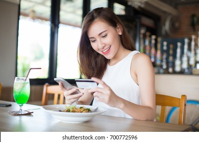 Asia woman using credit card and smart phone in restaurant