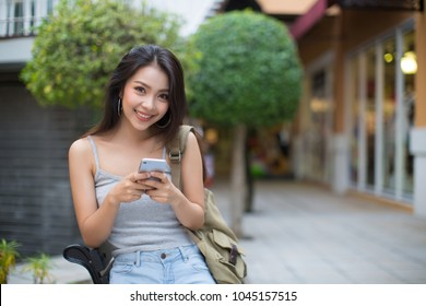 Asia woman using a smart phone in the street in a sunny summer day