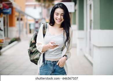 Asia woman walking and using a smart phone in the street in a sunny summer day