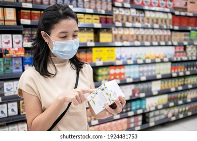 Asia woman wearing medical face mask and pick up tea from shelf. Reading nutritional value from the box. Shopping at supermarket in new normal style during coronavirus. Healthcare concept