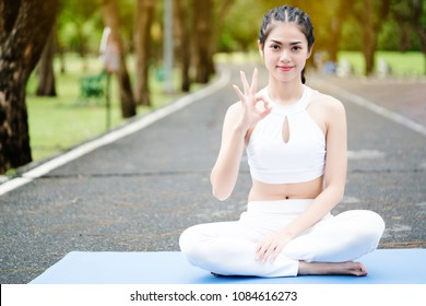 Asia woman wearing white gym clothes are practicing yoga in a garden with green trees. Yoga is the body's way to balance the body back again. Make good shape and free from disease.
