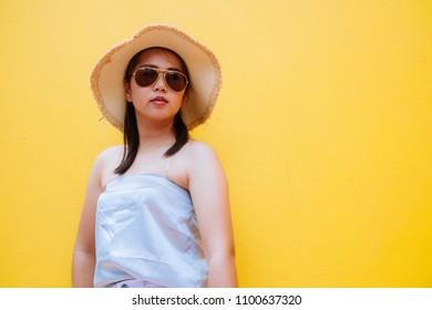 Asia women happiness with brim and sunglasses on yellow background.summer concept. vintage tone.