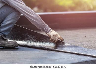 Asiatische Arbeiter installieren Teerfolie auf dem Dach des Gebäudes. Wasserdichte Anlage durch Gas- und Brandabfeuerung