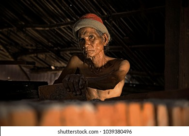 Asia worker man labor Thailand sitting on brick after work hard inside brick factory