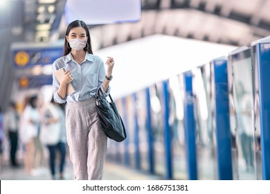 Asia working woman going to work and   wearing hygienic mask prevent corona virus and going to work at Sky train station