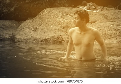asia young man enjoy in river at forest natural with retro filter
