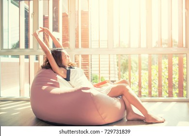 Asia young woman at home sitting on modern chair in front of window relaxing in her living room reading book, instagram toning