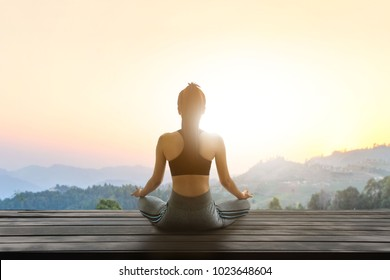 Asia young woman practicing yoga in nature at sunset