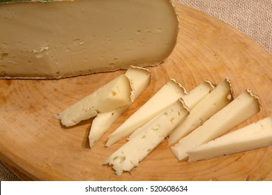 Asiago aged cheese produced in the Italian region of Veneto on a wooden cutting board in the mountain hut