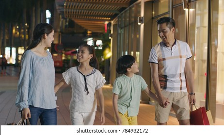 Asiam family laughing & walking outside shopping mall at night