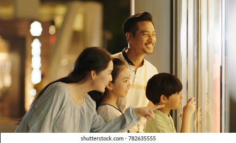 Asiam family laughing & watching store window outside shopping mall at night