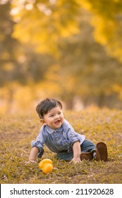 Asian 10-month old boy having fun outdoors in autumn