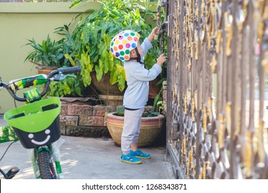 Asian 2 - 3 years old toddler boy child wearing safety helmet near his bike, Kid reaching up try to open gate of the house, Child want to escape to play, explore outdoor, Security and Safety Concept