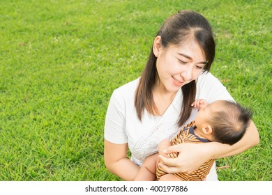 asian 2 months baby feeling happy and smiles with her mother in the garden and the sunset background